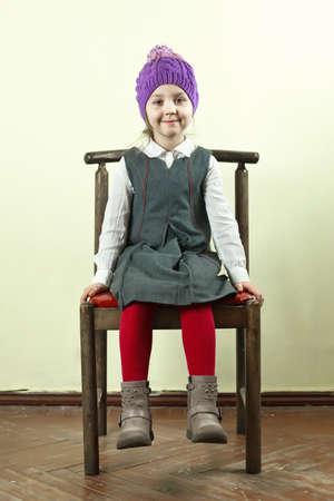 cuerpo completo: Sonriente ni�a posando en una silla en la habitaci�n