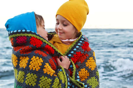girl friend: Boy and girl smiling to each other under a knitted plaid on the beach Stock Photo