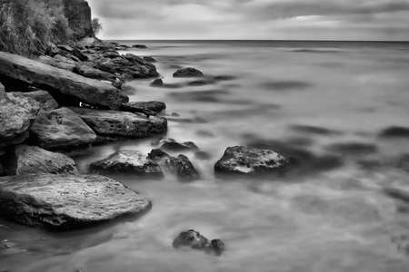 inhospitable: Black and white gloomy seascape before the evening storm. Long-exposure shot.