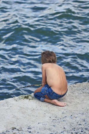 unclothed: 6-year old boy fishing on the concrete quay Stock Photo