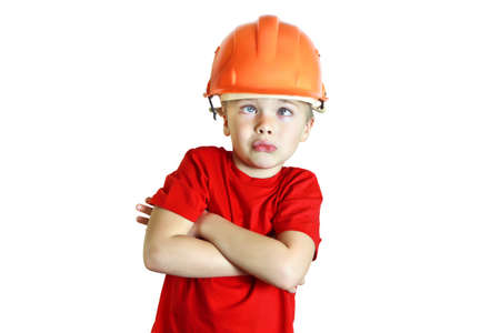 The blue-eyed boy of five in a red T-shirt and a construction helmet. He folded his arms. He squinted, looking up. Silly face. Studio photography on a white background. Jocular way. Occupation builder. Close-up.