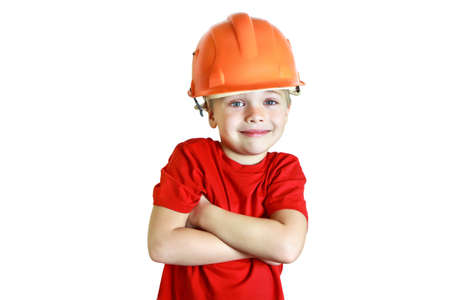 The blue-eyed boy of five in a red T-shirt and a construction helmet. He folded his arms. Smiling, looking at the camera. Joyful and cheerful facial expression. Studio photography on a white background. Jocular way. Occupation builder. Close-up. Stock Photo
