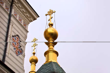 sacral: Gold crosses on kupoe black. The temple or church on a cloudy day. Gloomy skies. Rainy day. Details of the architectural ensemble. Taken from below. The religious building. Place of pilgrimage for Orthodox flock.