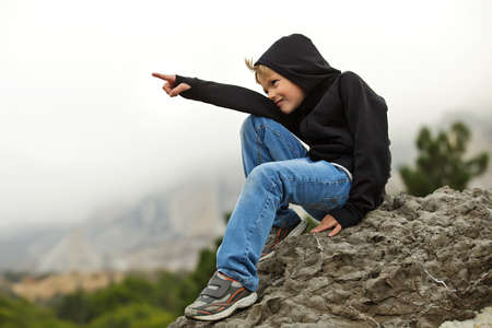 Boy teenager tourist sits on a rock and smiling. Man happy hike in the mountains. Against the background is seen the mountain and the forest, misty landscape and overcast sky. Coniferous forest, green trees. Boy sitting sideways to the camera, points his