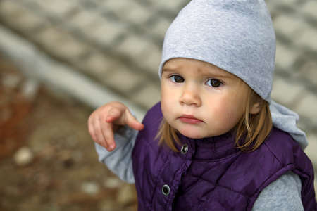 Cute sad little girl crying. Baby wearing a warm hat and jacket. Baby crying and pointing at someone. Its cold and cloudy. Photo close-up shot. Stock Photo