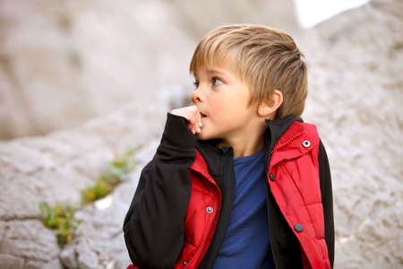 Boy in sports tourism clothes lying on a rock and smorit distance to Sauron. Child excited and bites his nails. He has a bad habit, nervous. Against the background of rocks and mountains. Boy is dressed in a black jacket and red waistcoat. Teen blond eigh