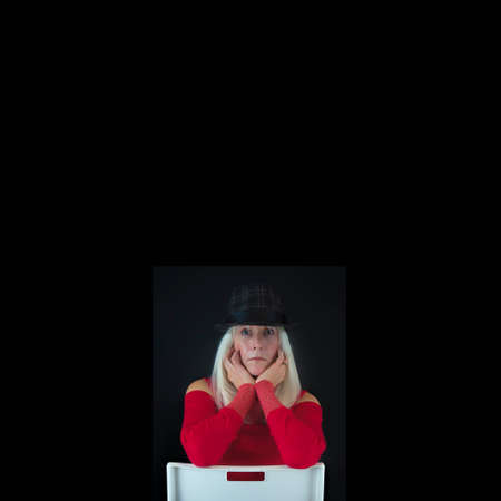 Minimalist Portrait with coys pace. of a mature woman with long white hair dressed in red sweater wearing a gray and black hat sitting on a backward white chair against a black background. Фото со стока