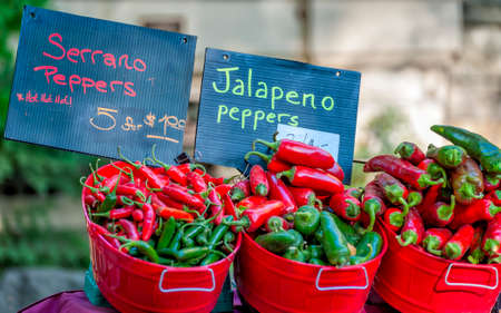 Jalapeno and Serrano peppers in red bushel baskets at Farmers Market