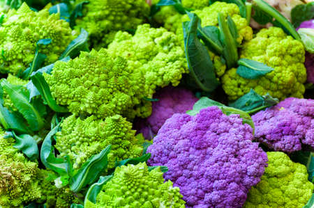 Close up of red and green cauliflower in different variety on display at farmers market