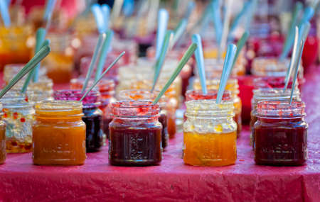 Portland,Oregon,USA - September 20, 2014:  Silver spoons in open jars are for sampling the jam before purchasing at Portland, Oregons South Park Blocks Farmers Market