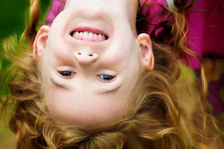 A close up of a little girl having fun hanging upside down while swinging.