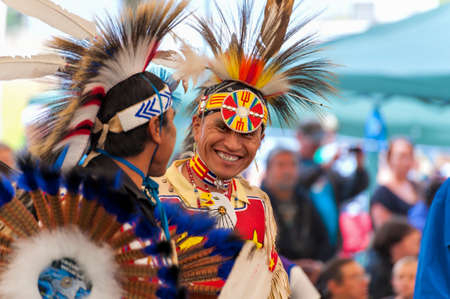 Portland, Oregon, USA - June, 14, 2014: Native Americans dressed in full regalia laughing and having fun at Delta Park annual Pow Wow in Portland Oregon