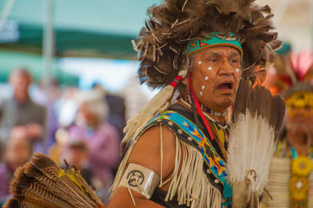 Portland, Oregon USA - June 14, 2014: Closeup of a Native American Indian dressed in full regalia chanting while dancing at Delta Park annual Pow Wow in Portland Oregon