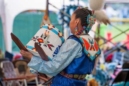 Portland, Oregon, USA - June, 14, 2014: A Native American Indian dances while holding a baby in a Papoose Cradleboard at the annual Delta Park Pow Wow in Portland, Oregon