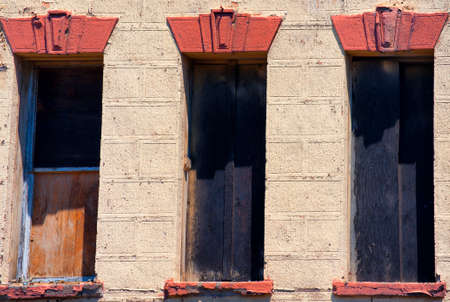 Section of an old abandonded building with boarded up holes where windows once were