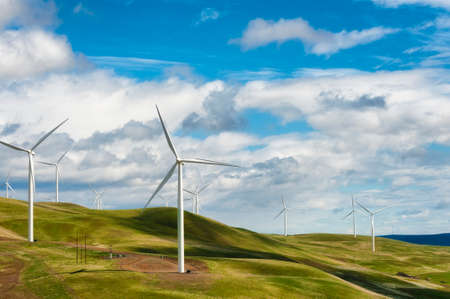 Wind Turbines stand tall and stark against the high desert landscape of rolling hills in the Columbia River Gorge Stock Photo