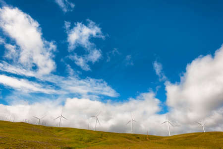 Windturbines stand tall and stark against the high desert landscape of rolling hills in the Columbia River Gorge