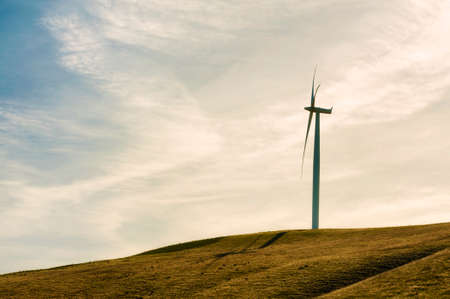 Wind Turbines stand tall and stark against the high desert landscape of rolling hills in the Columbia River Gorge Banque d'images