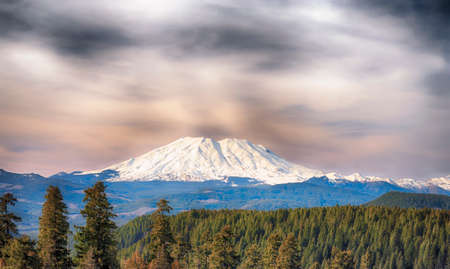 A view of Mt. St. Helens from the south.  Clouds layer the air above the snow covered Cascade volcano.
