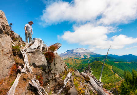 A hikerphotographer looks down from on top of Castle Peak, his tripod and camera close by with Mt. St. Helens in the background in Gifford Pinchot National Forest.