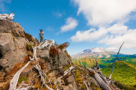 A hikerphotographer looks away from his tripod and camera, on top of Castle Peak with with Mt. St. Helens in the background in Gifford Pinchot National Forest.