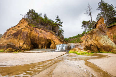 Hug Point waterfall full from a wet winter falls over low rock and onto the beach where it empties into the sea.   Surrounded on each side, by large sandstone rock formations, topped with wind shaped trees and shrubs. Stock Photo