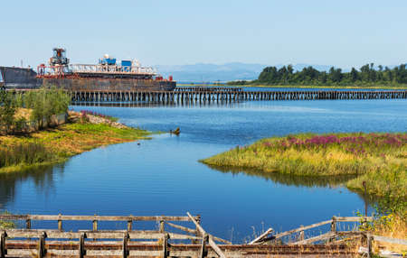An old rusted out ship docked on the Columbia River near Astoria, Oregon, railroad tracks in the foreground