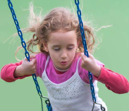 Girl dreamily swings ion a swing. 스톡 콘텐츠