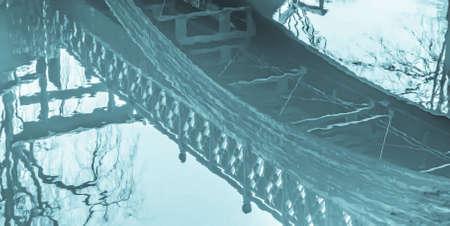 Waters reflecting a footbridge crossing. 스톡 콘텐츠