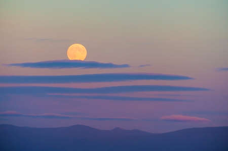 Harvest moon above the Cascade Mountain range.  The setting sun adds pastel colors to the sky while whispy clouds drift by.