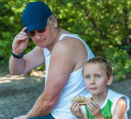 Grandpa and grandson taking a break while grandson eats a sandwhich.