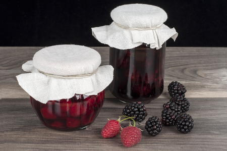 confiture: jar of homemade raspberry and blackberry confiture and fresh fruits