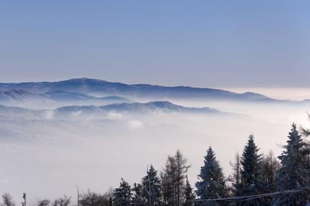 Montagnes d & # 39 ; hiver au-dessus au-dessus des nuages Banque d'images - 95119519