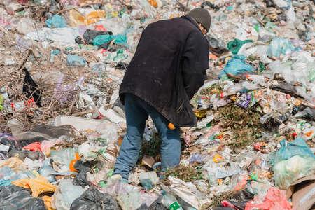 Ukraine, Tatarbunar - 13.04.2021: A man collects garbage at the city dump. City dump.
