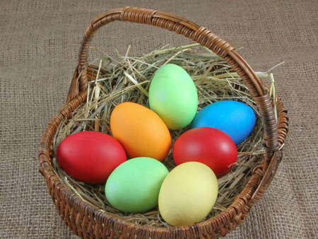 coloured Easter eggs with hay in a wicker basket