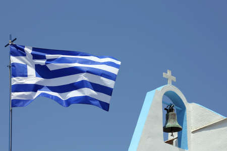 bell and cross of a small church and a greek flag Stock Photo