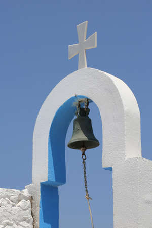 bell and cross of a small church in Greece Stock Photo