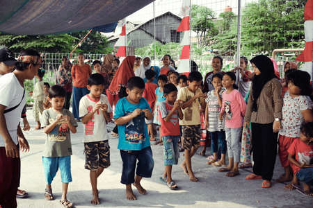 Jakarta, Indonesia - August 17, 2018: Little children are competing to put thread into needles on Indonesian independence day