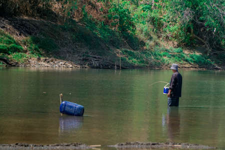 Old man fishing in the middle of the river Stok Fotoğraf