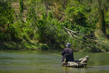 Old man is fishing in the middle of the river while sitting on a tree trunk