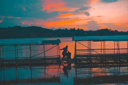 Purwakarta, West Java, Indonesia (03302018) : Someone is passing through the raft with a beautiful sunset background in Jatiluhur Dam