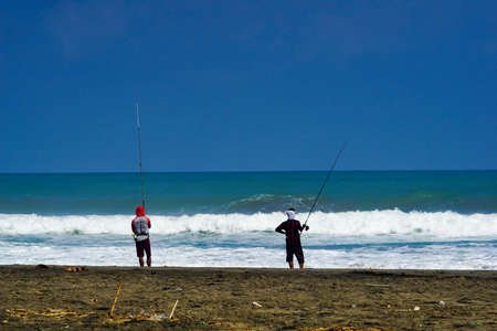 Kebumen, Central Java, Indonesia- June 17, 2018 : Fisherman are fishing by the beach with great waves
