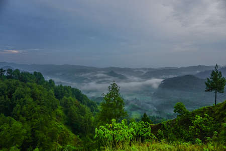 Beautiful landscape of green hills at sunrise. Buluh Payung Hill, Kebumen, Central Java, Indonesia Stock Photo