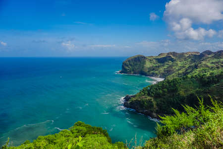View of landscape ocean and nice green hill on white clouds and Blue sky background. Kebumen, Central Java, Indonesia