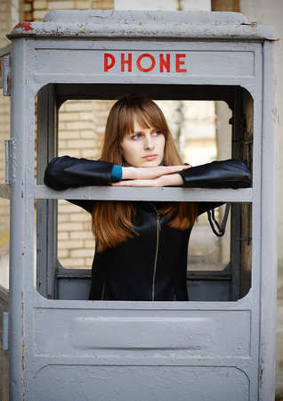 phonebox: lonely girl waiting ring in old phonebox