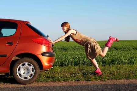 Pretty girl pushing a car photo