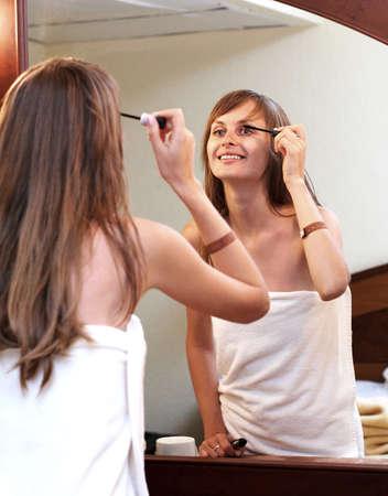 smiling girl applying black mascara photo