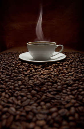 cup of steaming coffee with beans photo
