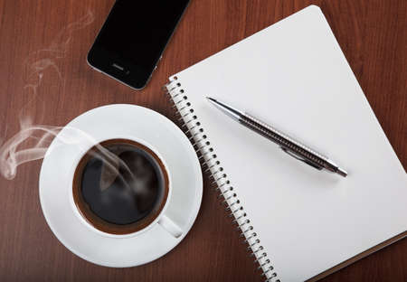 steaming coffee: coffee with blank notebook and phone