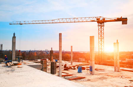 housing industry: tower crane at construction site in morning sunlight Stock Photo
